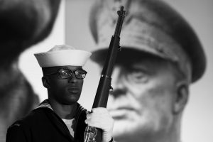 A NAVY SAILOR and member of an honor guard stands in front of a photograph of Gen. Dwight D. Eisenhower during the groundbreaking at the site of the Dwight D. Eisenhower Memorial in Washington on Thursday.