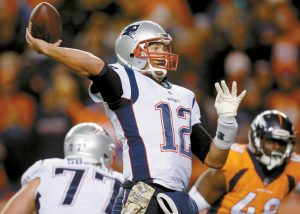 NEW ENGLAND PATRIOTS quarterback Tom Brady (12) throws as Denver Broncos outside linebacker Shaquil Barrett (48) pursues during the second half of an NFL football game on Sunday in Denver. The Pats rolled to a 41-16 victory over the Broncos.
