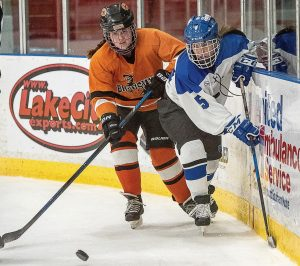 BRUNSWICK'S SHEA SULLIVAN and Lewiston's Nele te Loo (5) maneuver towards the puck during a Wednesday night hockey game at the Colisee in Lewiston.