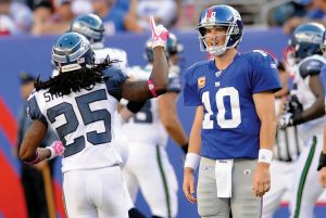 NEW YORK GIANTS QUARTERBACK Eli Manning, right reacts after throwing an interception against the Seattle Seahawks in early-season NFL action at East Rutherford, N.J. The Giants are struggling and looking to play younger players down the stretch.