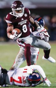 MISSISSIPPI STATE running back Kylin Hill (8) leaps over Mississippi defensive back Jalen Julius (7) on a 30-yard touchdown run during the second half of an NCAA college football game in Starkville, Miss., on Thursday. Mississippi won, 31-28.