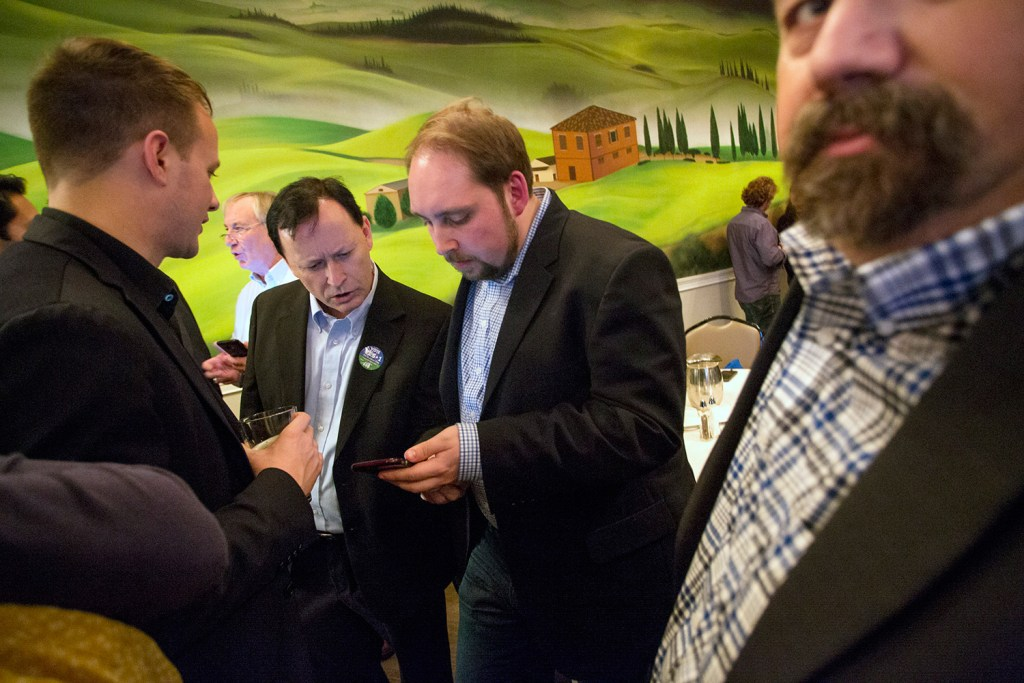 Shawn Scott, second from left, looks at a phone with campaign press secretary Michael Sherry while awaiting election results at Bruno's restaurant in Portland on Tuesday. Scott's company would have been the only one allowed to hold the license for a proposed York County casino, which failed at the ballot box.