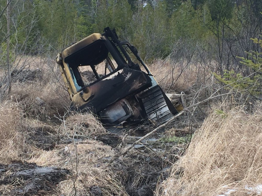 This bulldozer, owned by Cousineau Wood Products of Wilton, was found by hunters on Tuesday off Beech Hill Road in Sandy River Plantation, where it had been set on fire.