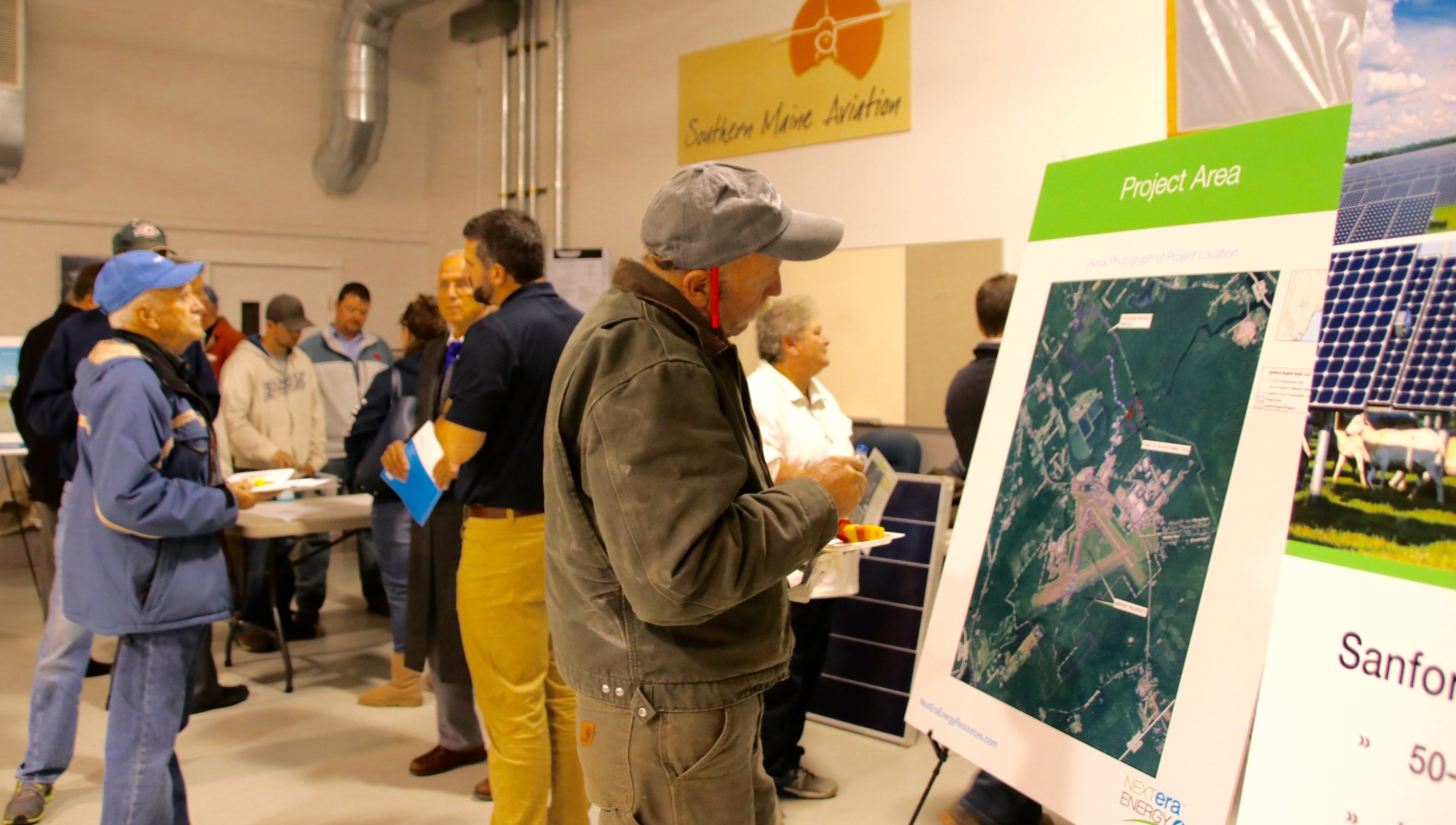 Participants attending an Open House event at Southern Maine Aviation at Sanford Seacoast Regional Airport on Tuesday checked out plans for NextEra's $69 million solar farm. The company plans to begin construction in 2018 with a view to begin generating power by 2019. TAMMY WELLS/Journal Tribune
