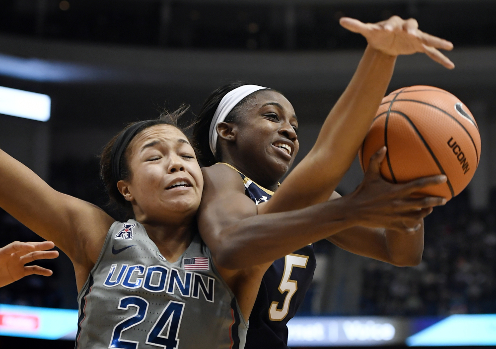 Napheesa Collier of Connecticut tangles with Jackie Young of Notre Dame while competing for a rebound Sunday during top-ranked UConn's 80-71 victory over the third-ranked Fighting Irish at Hartford, Conn.