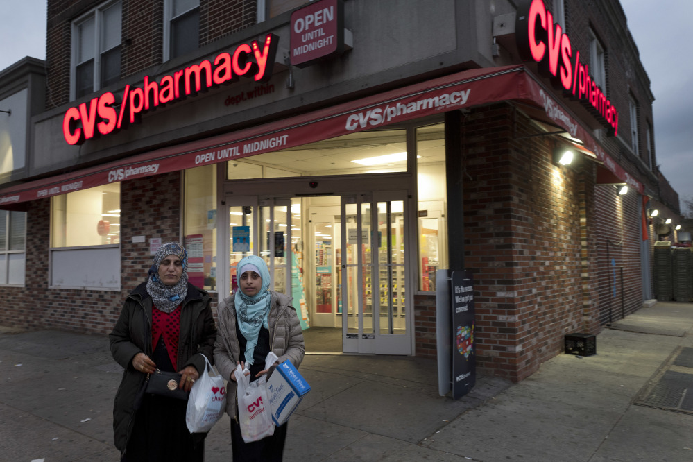 Customers leave a CVS Pharmacy, Sunday, Dec. 3, 2017 in the Brooklyn borough of New York. CVS will buy insurance giant Aetna in a roughly $69 billion deal that will help the drugstore chain reach deeper into customer health care and protect a key client, a person with knowledge of the matter said Sunday. (AP Photo/Mark Lennihan)