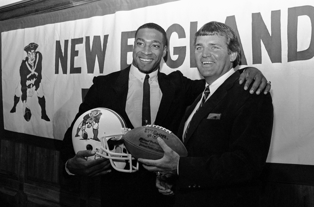 "FILE - In this April 11, 1984, file photo, newly signed New England Patriots football player Irving Fryar, left, poses with Patriots coach Ron Meyer during a press conference in Foxborough, Mass. From SMU's ""Pony Express"" to the NFL's infamous ""Snowplow Game,"" former college and professional football coach Ron Meyer was in the middle of some of the game's most controversial and colorful teams and moments in the 1980s. Meyer died Tuesday, Dec. 5, 2017, in Austin, Texas, at age 76.  (AP Photo/Ted Gartland, File)"