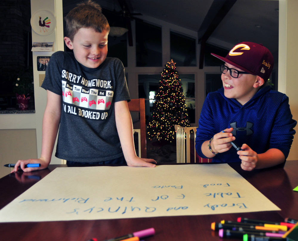 Quincy Emmons, left, and Brady Alexander work on a poster Thursday. They will staff a table Friday at the Richmond tree-lighting to collect for the Richmond Food Bank.