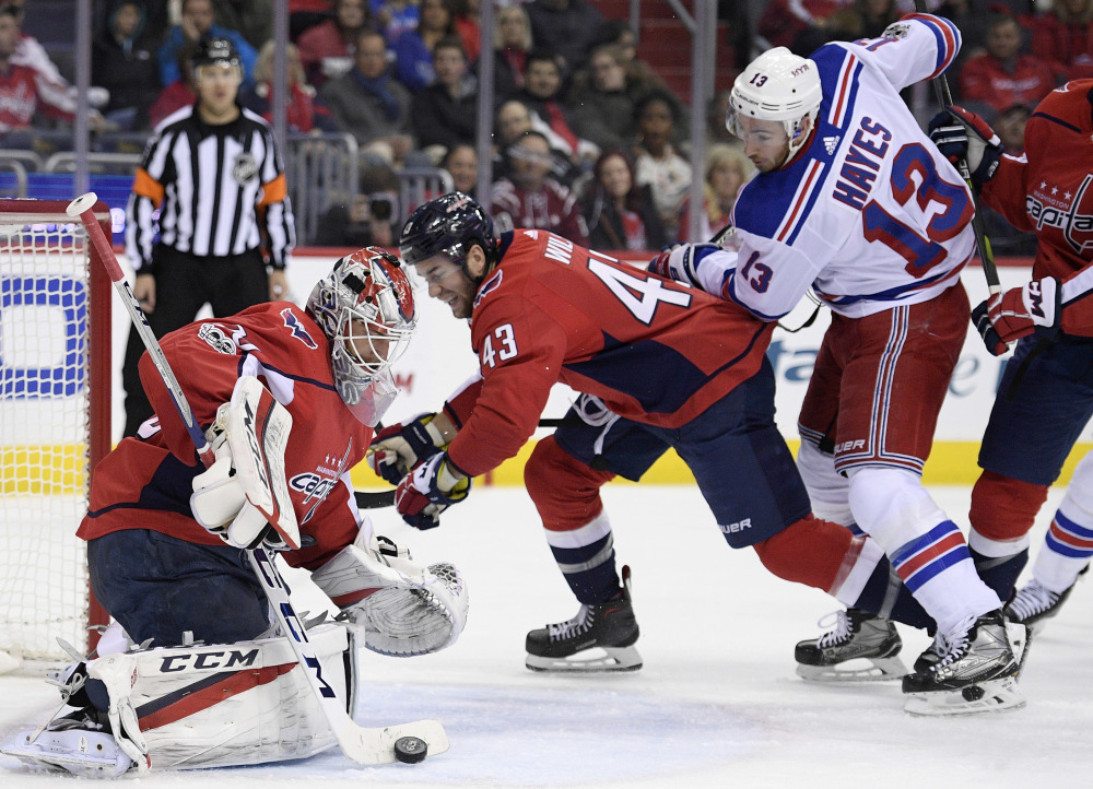Capitals goalie Braden Holtby stops the puck as Rangers center Kevin Hayes watches during the second period Friday night in Washington, D.C. Between them is Capitals right wing Tom Wilson.
