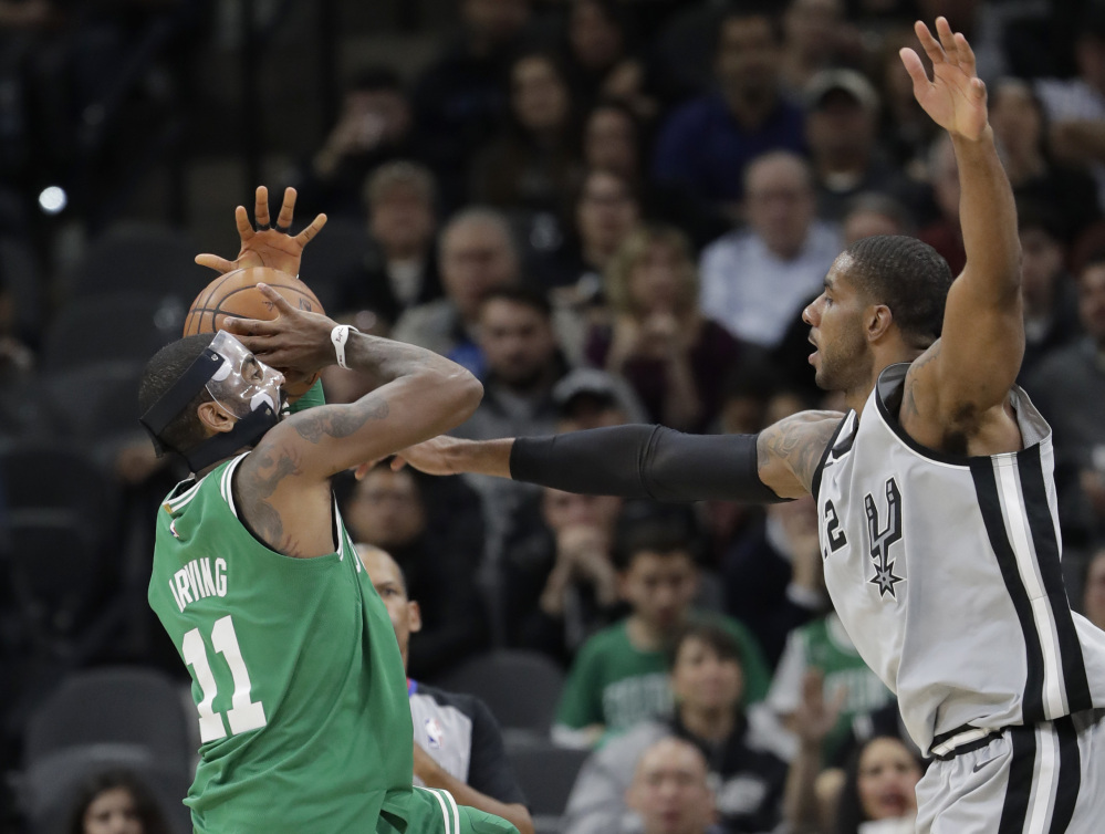 Celtics guard Kyrie Irving is fouled by San Antonio's LaMarcus Aldridge in the first half Friday night in San Antonio.