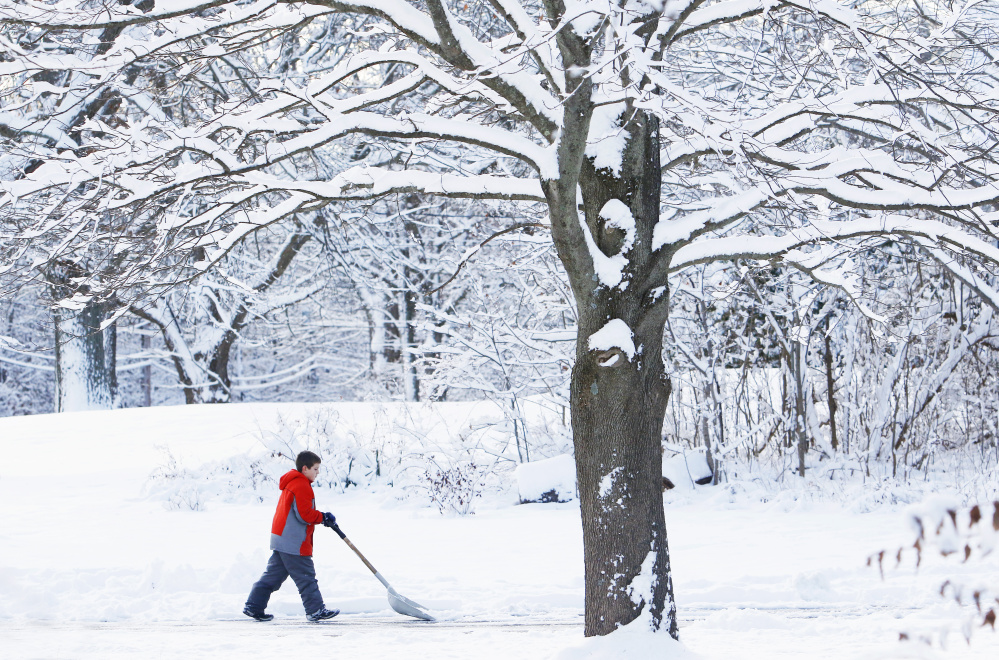 Gavin Brayne, 10, clears his driveway along Rogers Road in Kittery early Sunday following the first snowfall of the season.