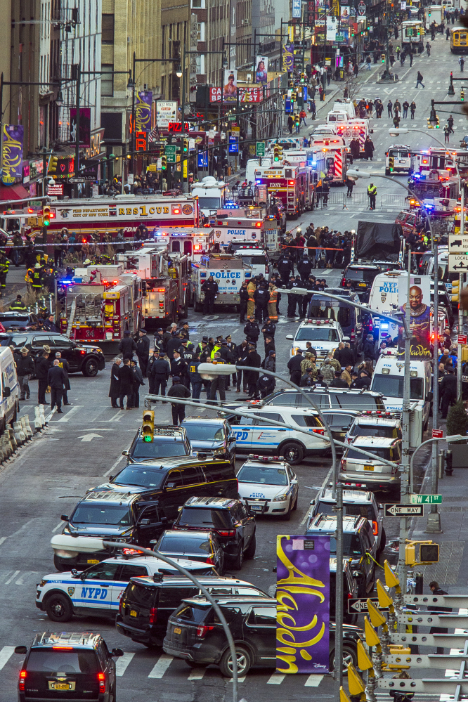 Law enforcement officials gather near New York's Times Square on Monday after a man with a pipe bomb strapped to him set off a crude bomb in an underground passageway of the subway system under 42nd Street. No one was injured except the would-be suicide bomber.