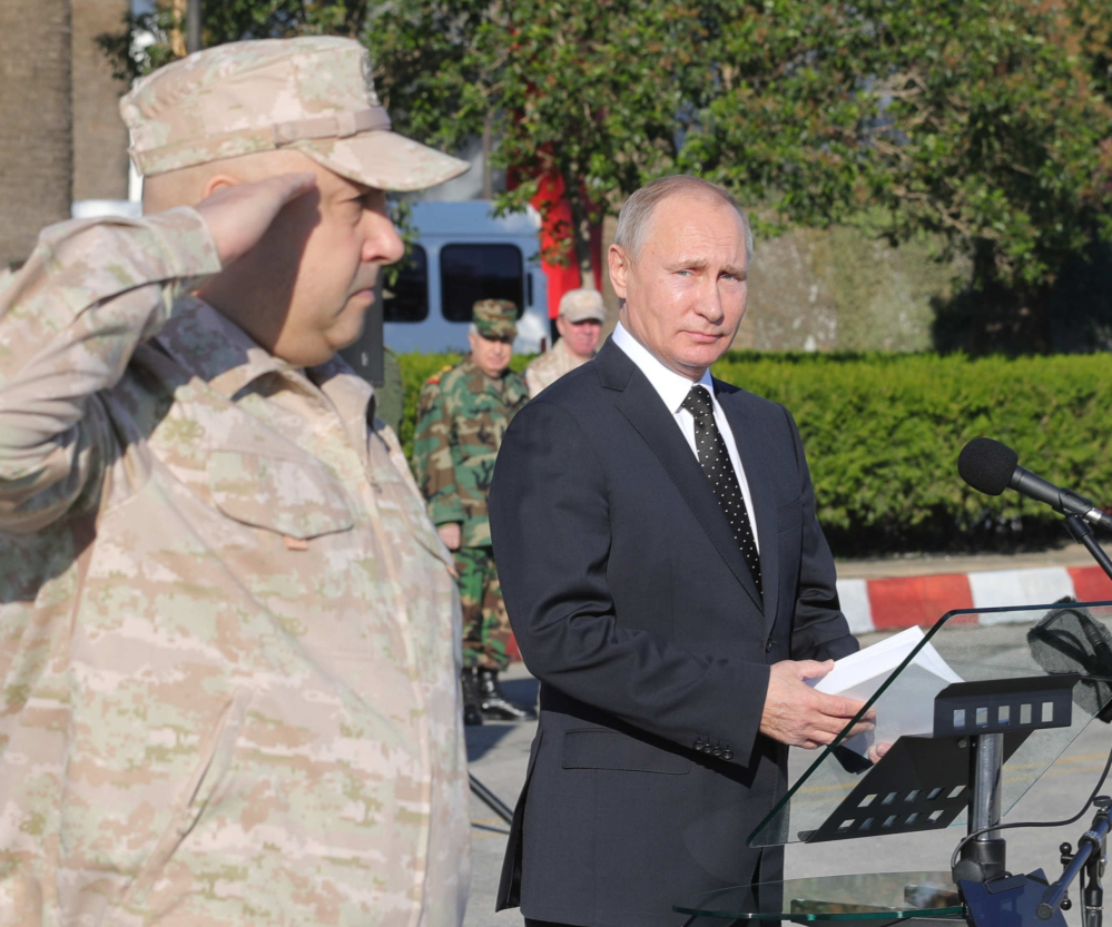 Russian President Vladimir Putin appears in Syria on Monday with Col. Gen. Sergei Surovikin, his commander there.