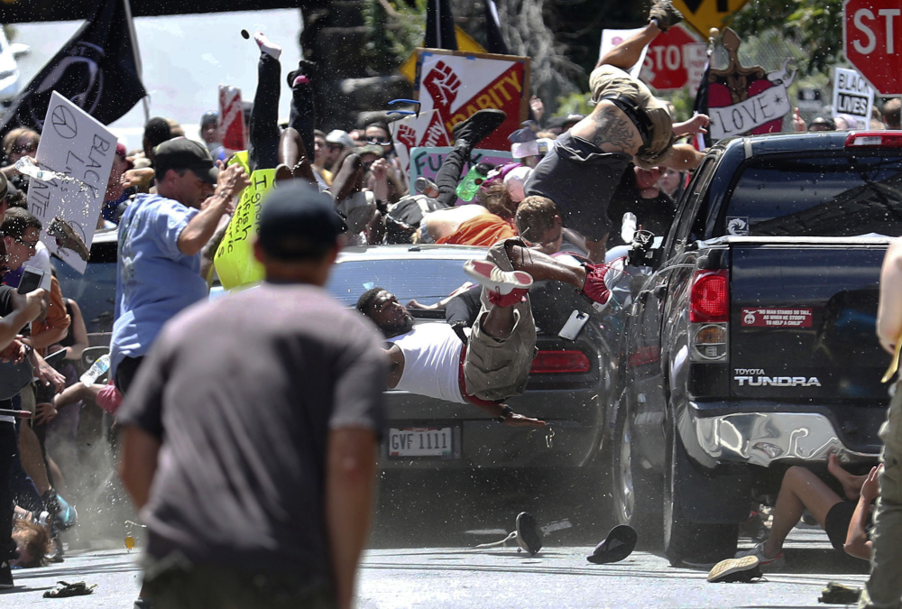 People are thrown into the air as a car drives into a group of protesters demonstrating against a white nationalist rally in Charlottesville, Va., on Aug. 12, 2017. The white nationalists were holding the rally to protest plans by the city of Charlottesville to remove a statue of Confederate Gen. Robert E. Lee. There were several hundred counterprotesters marching in a long line when the car drove into a group of them.