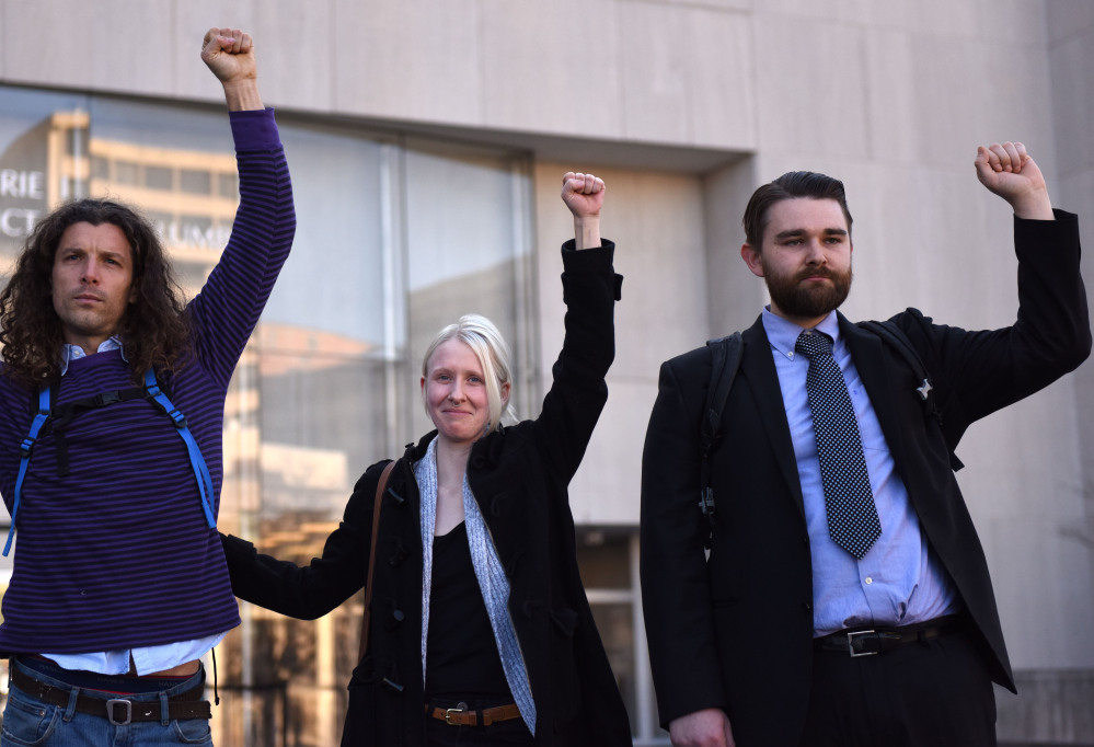Brittne Lawson, center, Alexei Wood, left, and Oliver Harris raise their arms after receiving a not guilty verdict in the the first of the presidential inauguration riot trials on Dec. 21, 2017.   MUST CREDIT: Washington Post photo by Michael Robinson Chavez