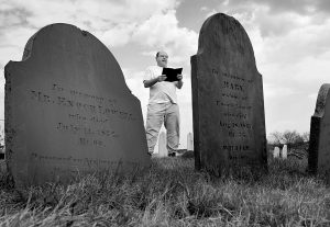 WALTER SKOLD OF FREEPORT reads a Henry Wadsworth Longfellow poem while posing in Eastern Cemetery in Portland in this 2010 photo. Skold, the founder of the Dead Poets Society of America who has visited the graves of more than 600 bards, has commissioned John Updike's son to carve his own tombstone in 2017 in Newburyport, Mass.