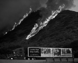 FLAMES FROM THE THOMAS FIRE burn above a truck on Highway 101 north of Ventura, California, on Wednesday.