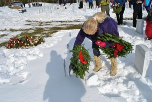 Wreaths were laid on the graves of veterans on Wreaths Across America day at the Southern Maine Veterans' Cemetery in Springvale on Saturday. Heidi Yeaton lays a wreath on the grave of her brother-in-law, William Chapais who served in the U.S. Army. DINA MENDROS/Journal Tribune