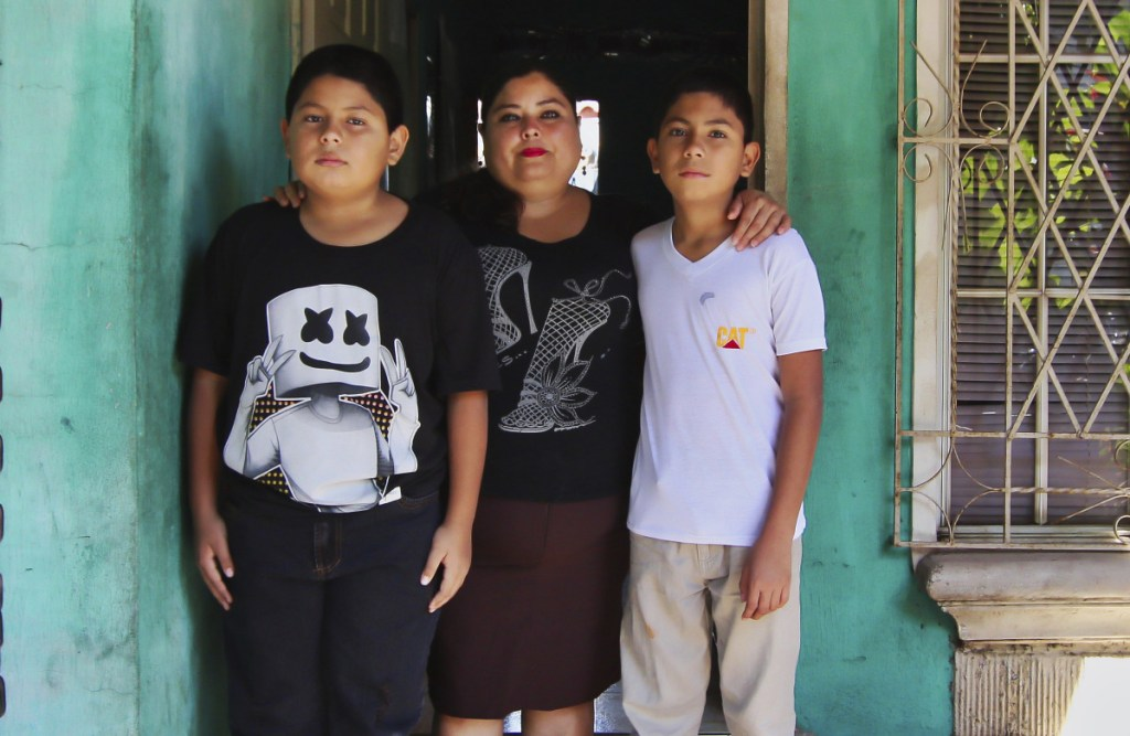 Flor Tovar and her sons, Christian, right, and Omar Elias, use cash wired from her husband in the U.S. to get by.