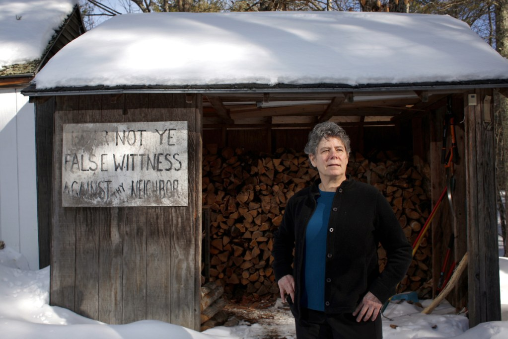 "Anne Gass, shown outside her woodshed in Gray, says, ""I'm very excited to see so many women are willing to step up at this point and say no more."" The sign on Gass' shed was a prop in a play."