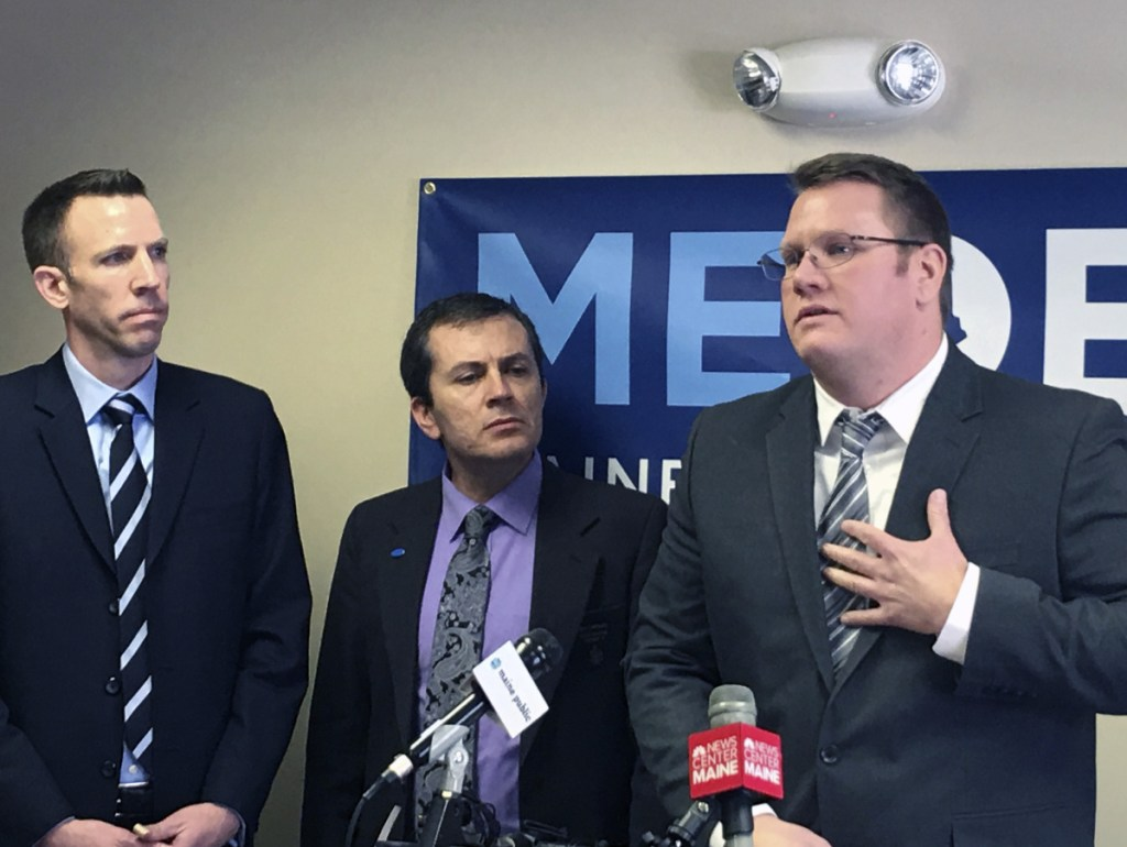 Phil Bartlett, left, chair of the Maine Democratic Party, and state Sen. Ben Chipman, D-Portland, listen Thursday as Andrew Kiezulas discusses how addicts in recovery can reclaim their life.