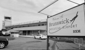 """BRUNSWICK EXECUTIVE AIRPORT'S air operations building, as seen in 2014. In its proposal to Amazon, the Midcoast Regional Redevelopment Authority states: """"We believe that we could support a large satellite facility for the New England region, as well as a research and development site for drone operations."""""""