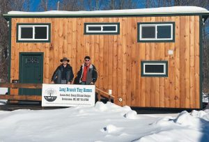 JOHN FAVREAU, left, and Pete Feeney stand outside of a completed solar-powered tiny home at Long Branch School and Tiny Homes.