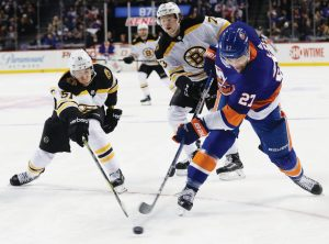 NEW YORK ISLANDERS forward Anders Lee (27) shoots the puck past Boston's Ryan Spooner (51) as Charlie McAvoy (73) moves in during the second period of an NHL hockey game on Tuesday in New York. The Bruins pulled away for a 5-1 victory.