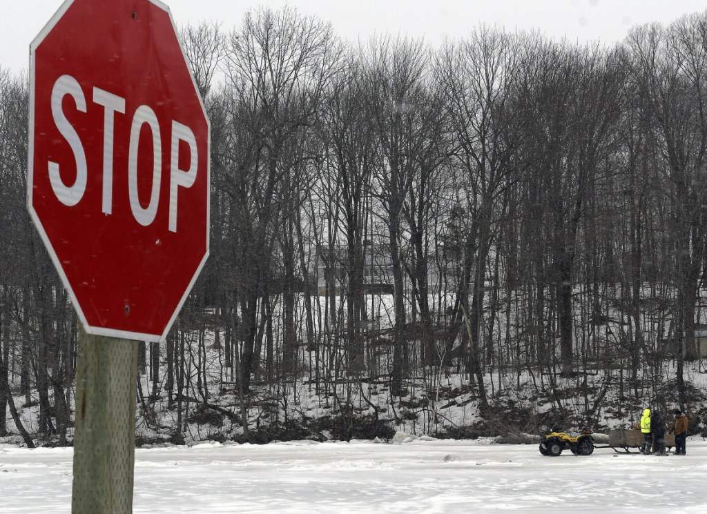 The crew at Baker's Smelt Camps in Pittston prepares to cut holes through the ice Tuesday on the Kennebec River after the Coast Guard announced it would stop trying to break through. Workers had erected a sign in the river to deter icebreakers from traveling farther upriver.