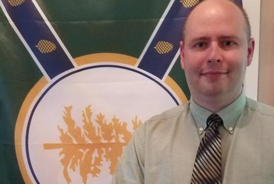 Jackman Town Manager Tom Kawczynski poses in front of his New Albion flag.
