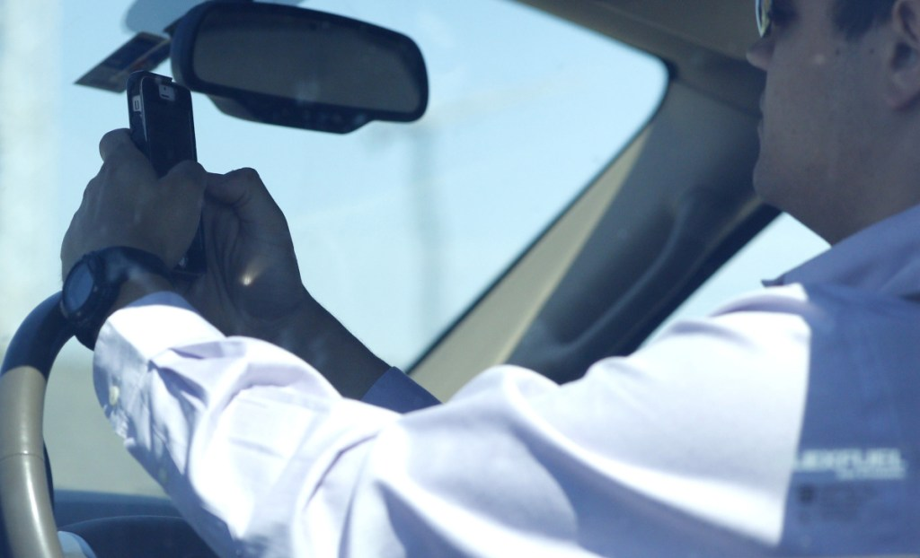 A man looks at his phone while driving down Woodall Rodgers Freeway in Dallas, Texas, in 2015.