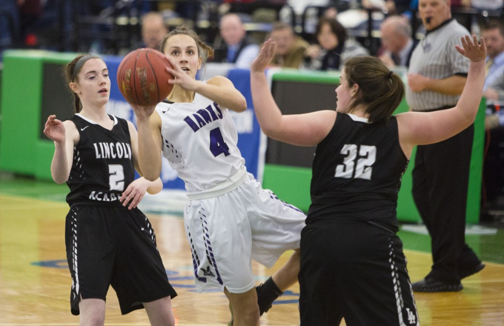 Marshwood guard Nathalie Clavette drives past Lincoln Academy's Alison York, left, and Isabelle Sawyer during a girls' basketball Class A South quarterfinal at the Portland Expo on Monday.