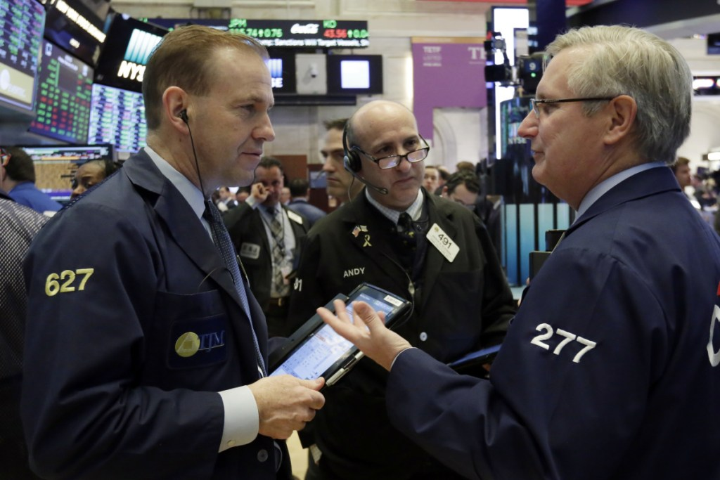 From left, traders Michael Smyth, Andrew Silverman and Christopher Fuchs work Friday on the floor of the New York Stock Exchange. Technology companies, banks and health care stocks accounted for much of the market's gains.