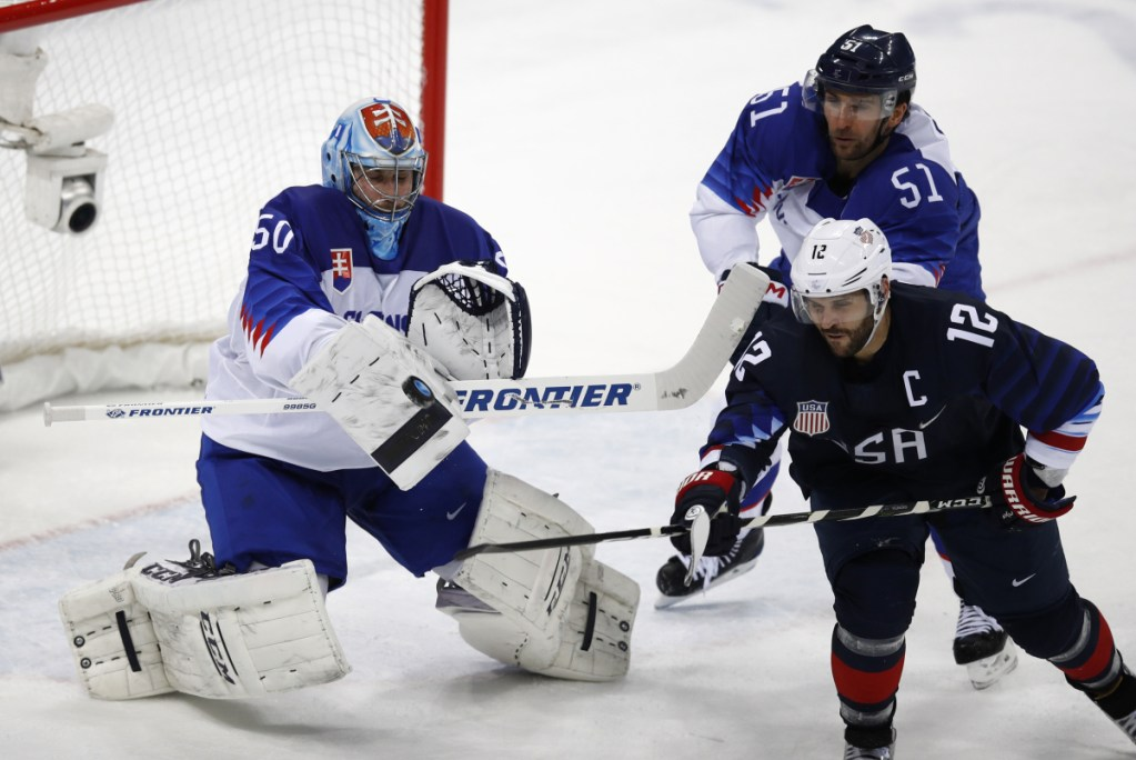 U.S. goalie Ryan Zapolski deflects a shot as Brian Gionta and Dominik Granak of Slovakia battle for position. Gionta will return to Boston, where he spent four years at Boston College.