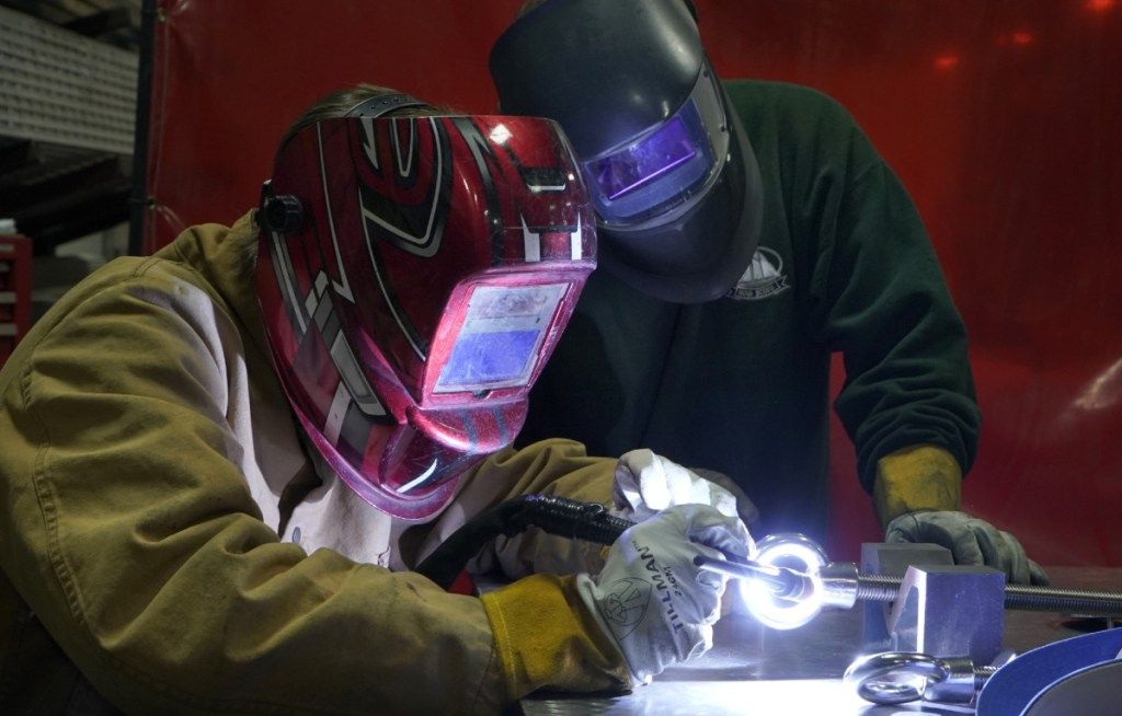 """Sam Roy, 17, welds at DeepWater Buoyancy under the watchful eye of Joe Woods, a welder-fabricator at the maker of subsea buoyancy products. """"Something just clicked"""" when he took a welding class, said Roy, adding: """"I found it more interesting than anything I'd done before."""""""