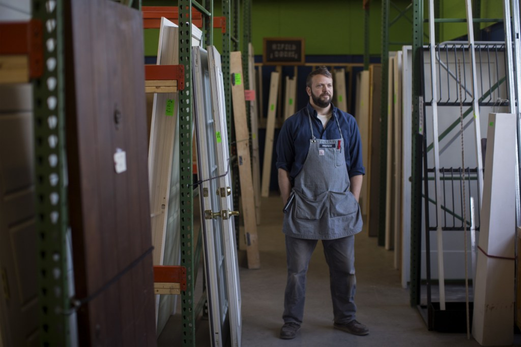 Andrew Smith, near some of the repurposed doors and windows for sale at ReStore in Portland.