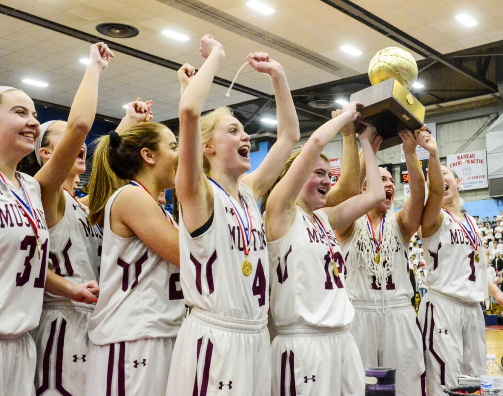 The Monmouth Academy girls' basketball team celebrates with the Gold Ball after beating Houlton to win the Class C state championship on Saturday at the Augusta Civic Center.