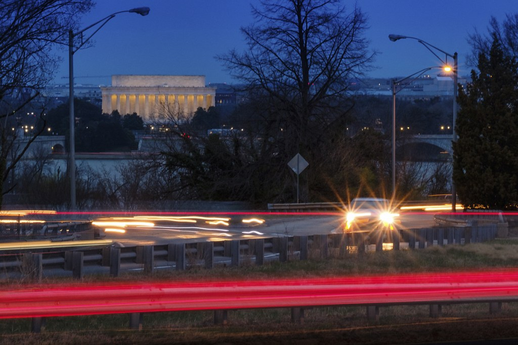 Traffic streaks along U.S. Highway 50 early in the morning Friday across the Potomac River from Washington in Arlington, Va. The Trump administration is expected to announce that it will roll back automobile gas mileage and pollution standards that were approved during the Obama administration.