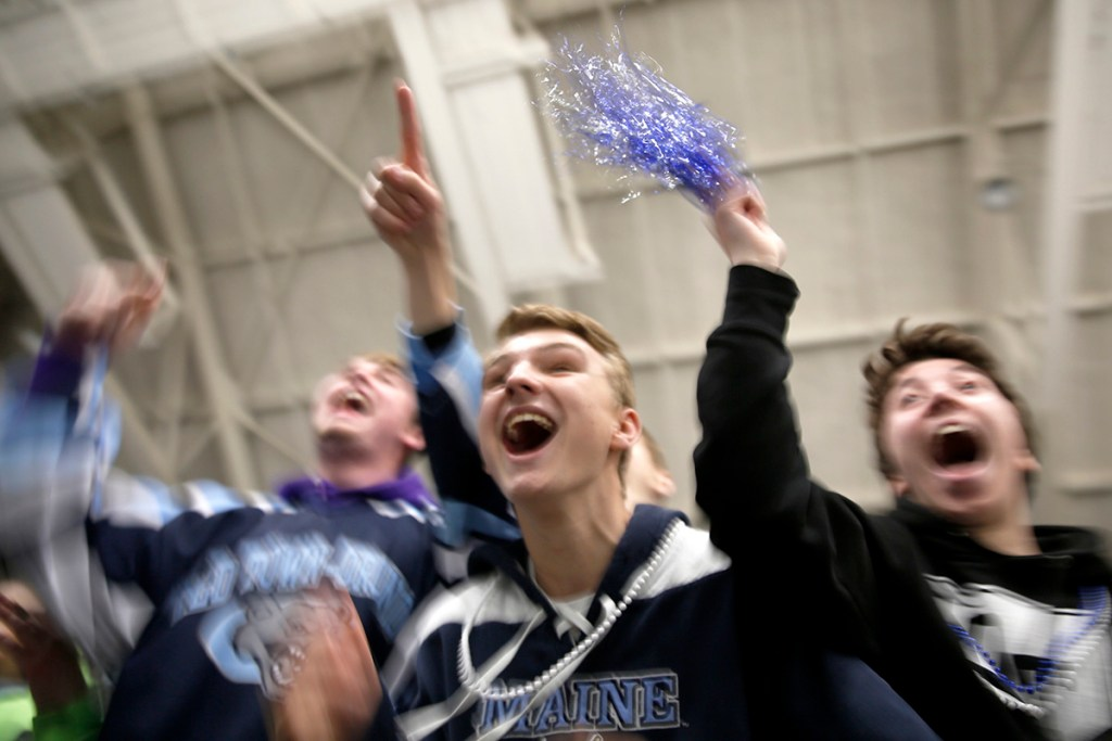 Chris Albert, center, a sophomore at Old Town High School, celebrates with classmates after Old Town/Orono beat Greely, 3-2, in overtime in the Class B state championship hockey game in Lewiston on March 10.