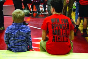 The Wells High School wrestling team won its second straight state championship but what the Warriors are most proud of is their work with former Wells wrestler Nate Smith's son, Spencer, who is fighting Sanfilippo Syndrome. Wells has raised money all season every time one of the wrestlers gets a win. They are expecting the total to be close to $10,000. Spencer is pictured sitting with Wells' Jonathan Brown watching the Class B state meet at Wells High School. Amy Murphy Photography
