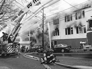 FIREFIGHTERS try to bring a morning fire at 45 Hill St. in Biddeford under control on Monday. The five-alarm blaze left 24 residents of the 118-year-old building homeless. ED PIERCE/JOURNAL TRIBUNE