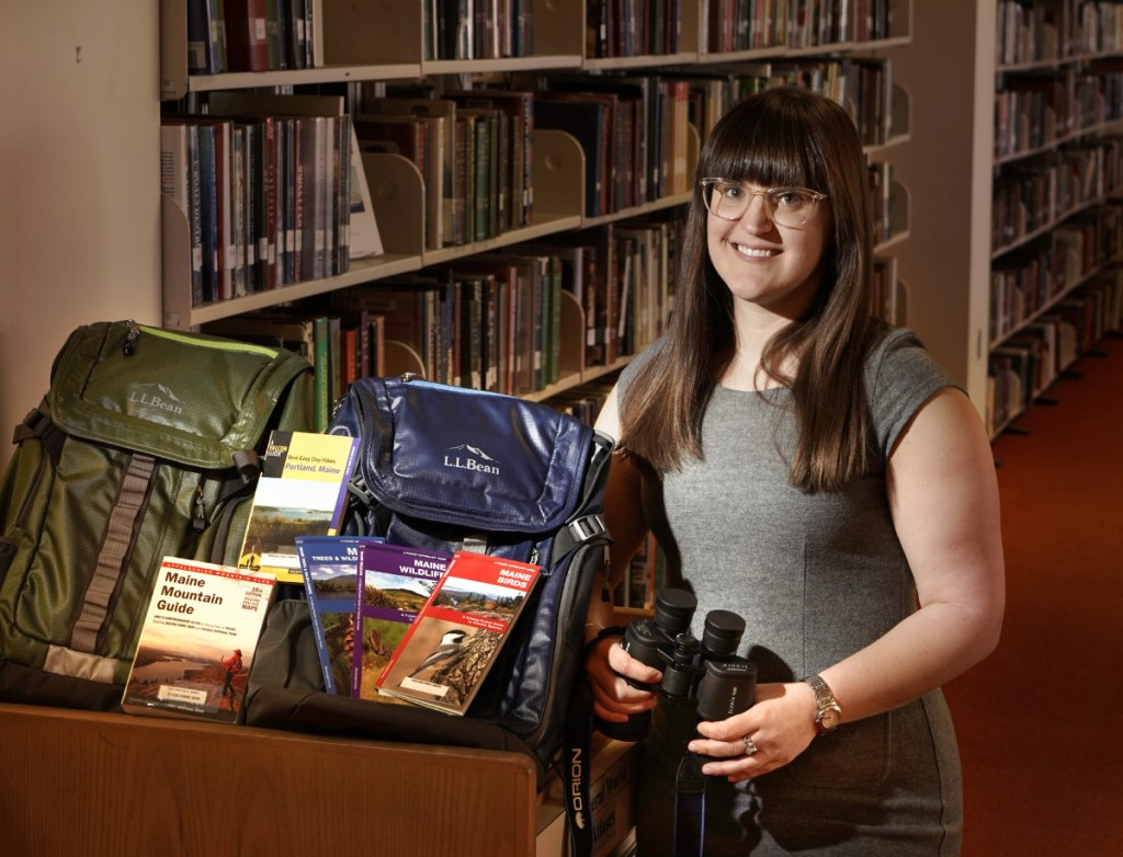 Meg Gray, science and technology librarian at the Portland Public Library, with backpacks that will be available to be checked out filled with items geared toward hiking, birding and stargazing. Gray is also saving seeds that library patrons will be able to check out.