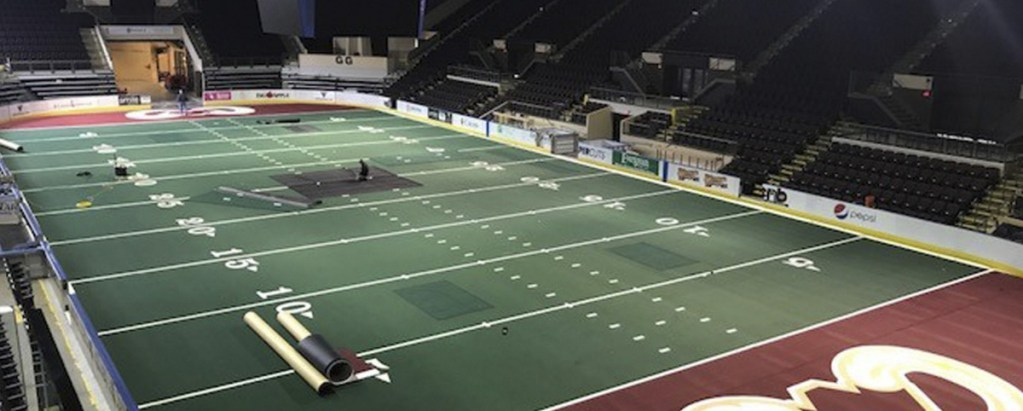 Workers at Cross Insurance Arena lay turf to prepare for the Maine Mammoths' April 14 home opener against the Carolina Cobras.