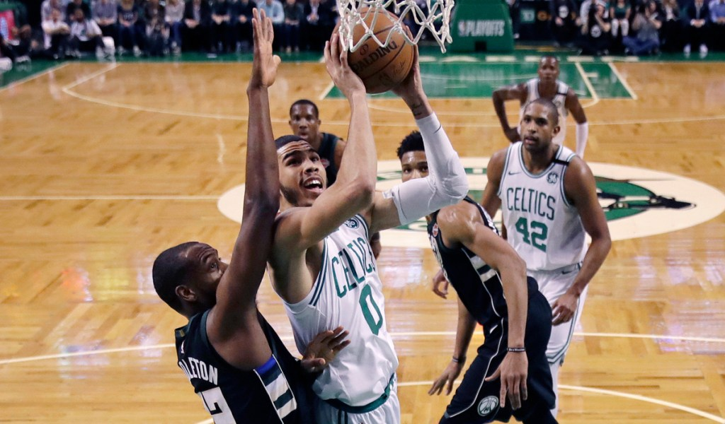 Boston's Jayson Tatum drives to the basket against Milwaukee forward Khris Middleton, left, during the first quarter of Tuesday Game 2 in Boston. The Celtics won to take a 2-0 series lead.