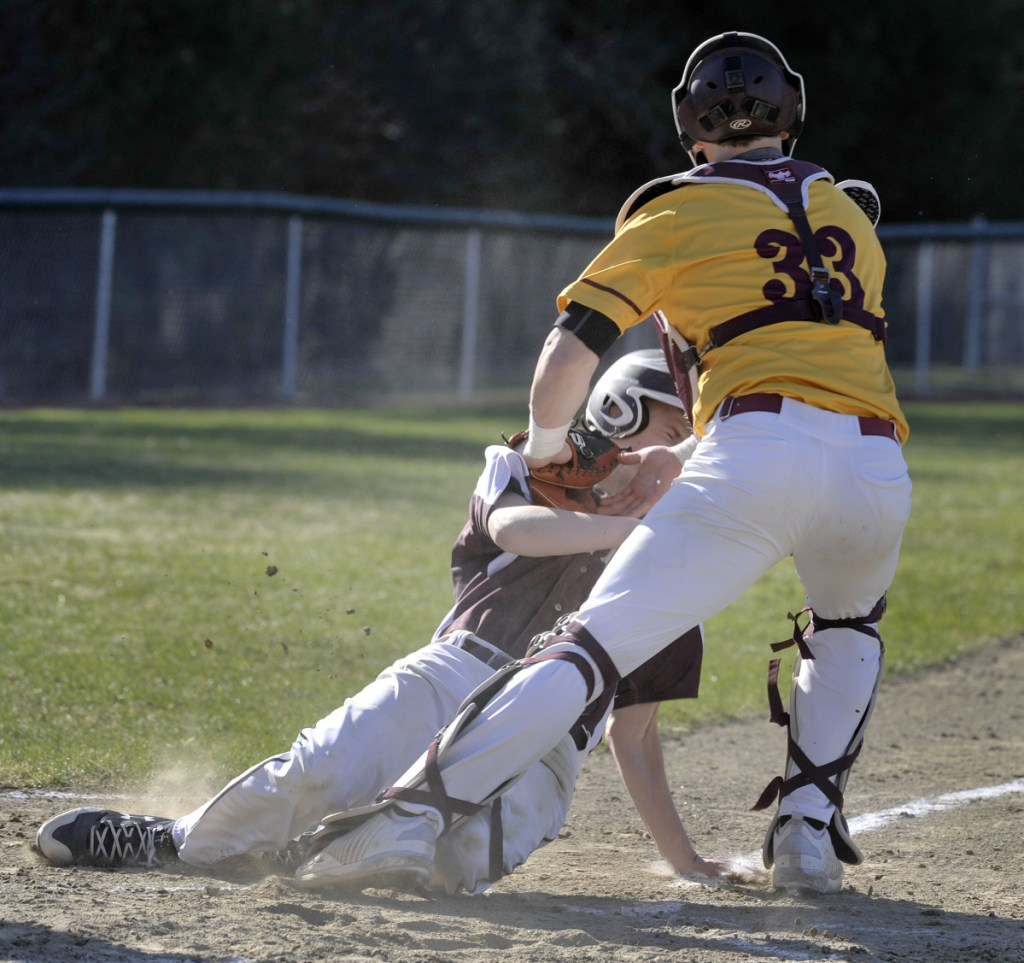 Cape Elizabeth catcher Brendan Tinsman tags out Connor Sullivan of Greely on a throw from center fielder Jameson Bakke during the third inning Monday. The Capers went on to a 4-1 victory in 13 innings at Cumberland.