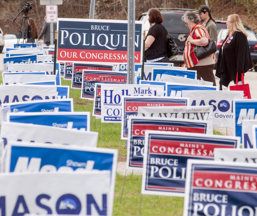 During lunch break Friday, people walk past signs outside the Augusta Civic Center during the Maine Republican Party convention. (Staff photo by Joe Phelan/Staff Photographer)
