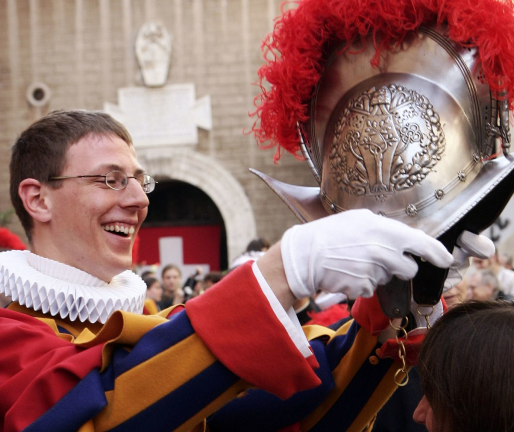 An unidentified Swiss Guard admires his metal helmet at the Vatican.