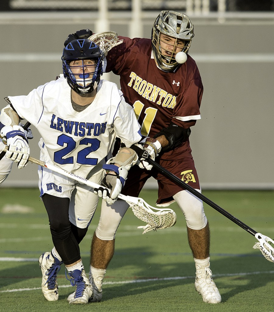 Brayden Charest, left, of Lewiston and Cameron Houde of Thornton Academy battle for the ball during Thornton's 15-9 lacrosse victory Thursday in Lewiston.
