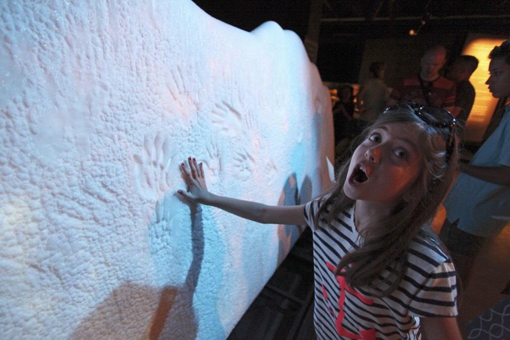 """Dinah Routhier, 9, reacts after placing her hand on a sample """"glacier"""" at """"Titanic: The Artifact Exhibition"""" at the Portland Science Center."""