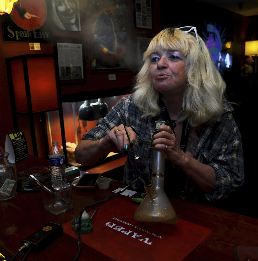 "Linda Wood smokes pot at the Speakeasy Vape Lounge in Colorado Springs. The veto of a bill allowing ""tasting rooms"" means clubs like Speakeasy can keep operating unregulated."